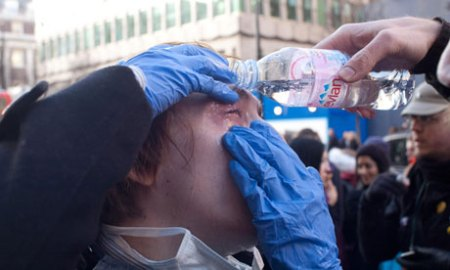 A man washes his eyes after police used CS gas on tax protesters