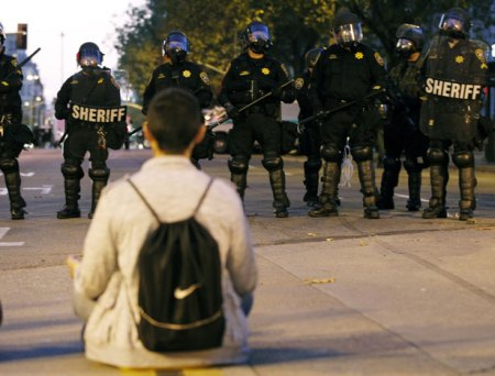 A man sits in front of a police line at City Hall during an anti-Wall Street protest in Oakland, California, 25 October 2011. (REUTERS/Kim White)