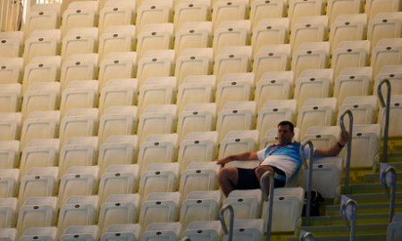 A spectator sits alone on the first day of Olympic swimming at the Aquatics Centre