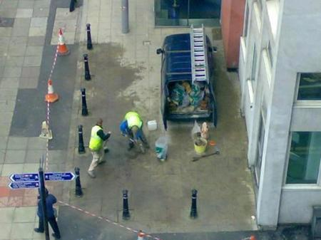 Workmen installing cast-iron bollards to prevent vehicle access