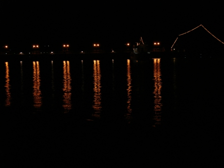 lights from pier reflected in the sea