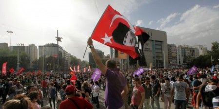 A man waves a flag with portrait Turkey's founder Kemal Ataturk as thousands of Turkish youths gather at city's main Kizilay Square in Ankara, Turkey, Sunday, June 2, 2013. (Burhan Ozbilici/AP)