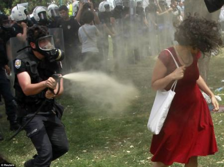 The woman in red turns as the policeman showers her in pepper spray at close range