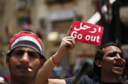 A protester, opposing Egyptian President Mohamed Mursi, holds a sign during a protest demanding Mursi to resign at Tahrir Square in Cairo