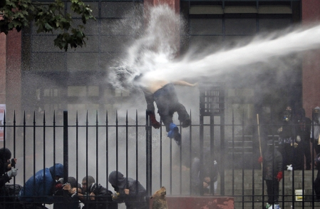 A student is knocked off a fence by a jet of water sprayed by riot police, during a protest against the government to demand changes in the public state education system, in Santiago, Chile, on June 26, 2013. (Reuters/Carlos Vera)