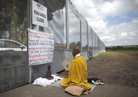 Japanese Buddhist Monk and Anti-nuclear campaigner Toyoshige Sekiguchi prays at the outer security gate leading to the G8 summit in Enniskillen, Northern Ireland, on June 18, 2013. Sekiguchi, from Japan, spent the last nine days walking from Belfast to Enniskillen carrying a banner and beating a small drum. The 48-year-old said he has been marching for peace since 2009, and last year walked 200 miles from Pittsburgh, Pennsylvania, to the USA's G8 summit venue at Camp David, in Maryland. (Peter Muhly/AFP/Getty Images)