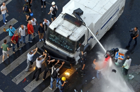 Protesters try to stop an armored crowd control truck from which the riot police fire water cannon at Taksim Square in Istanbul, on June 22, 2013. Turkish riot police fired water cannon to clear thousands of protesters from Istanbul's Taksim Square on Saturday, the first such confrontation there in nearly a week. (Reuters/Marko Djurica)
