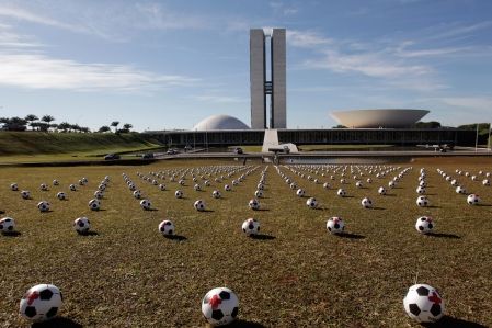 Soccer balls representing lawmakers lay in rows outside Congress as part of a protest against spending on the Confederations Cup soccer tournament in Brasilia, Brazil, on June 26, 2013. The wave of protests that hit Brazil on June 17 began as opposition to transportation fare hikes, then expanded to other causes including anger at high taxes, poor services and high World Cup spending, before coalescing around the issue of rampant government corruption. (AP Photo/Eraldo Peres)