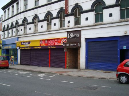 row of closed and boarded-up shops