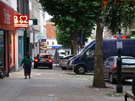 cars forcing their way past market stalls in pedestrianised street