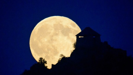 supermoon rises above the castle of Somoskoujfalu, northeast of Budapest, Hungary